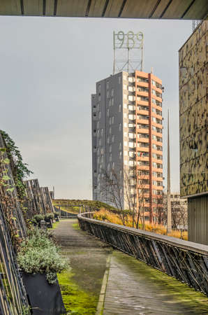 Rotterdam, The Netherlands, November 24, 2019: footpath in the Kop van Zuid neighbourhood, leading up to a residential tower with it's year of construction 1989 on top
