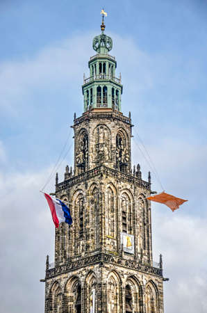 Groningen, The Netherlands, December 7, 2019: the tower of Martinikerk (St. Martin's church) with the Dutch red, white and blue flag as well as an orange flag