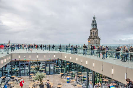 Groningen, The Netherlands, December 7, 2019: many people on the roof of the recently completedForum building enjoy the view of the town and Martini church