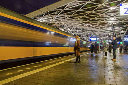 Tilburg, The Netherlands, December 6, 2019: people waiting on the platform while a Dutch Railways intercity enters the station