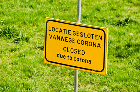 Rotterdam, The Netherlands, April 8, 2020: green lawn with yellow sign stating in Dutch and English: location closed due to corona, as part of municipal covid-19 measures Editorial