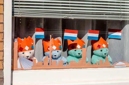 Rotterdam, The Netherlands, April 26, 2020: four teddy bears with Dutch flags placed in a window for the
