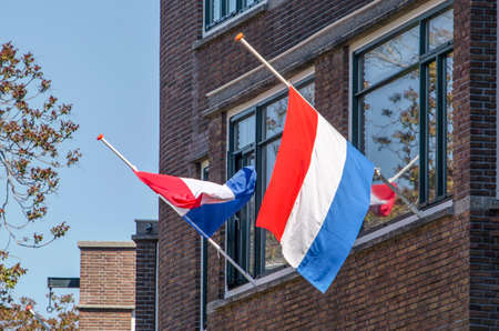 Rotterdam, The Netherlands, May 4, 2020: two flags half-mast in a residential street on Remembrance Day, 75 years after the end of World War Two