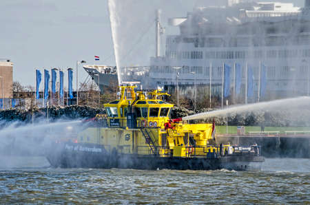 Rotterdam, The Netherlands, March 21, 2020: Port of Rotterdam fire boat spouting water on Nieuwe Maas river with former cruiseship SS Rotterdam in the background Editorial