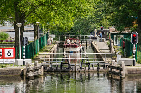 Rotterdam, The Netherlands, May 15, 2020: small yacht in a little sluice in Noorderkanaal canal waiting for the sluice doors to open