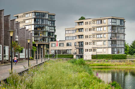 Zwolle, The Netherlands, August 2, 2020: recently built apartment buildings and quay houses facing lake Milligerplas 新闻类图片