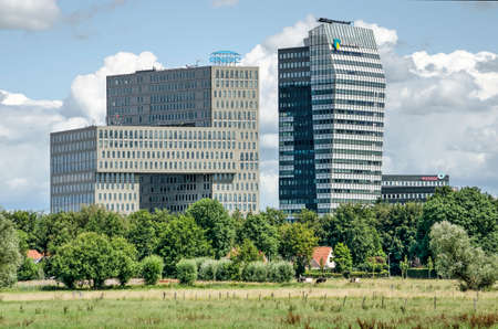 Zwolle, The Netherlands, July 21, 2020: long distance view of two large modern office buildings at Voorsterpoort area, with a contrasting rural landscape in front of them 新闻类图片