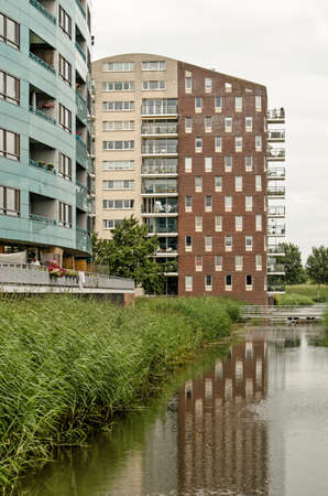 Zwolle, The Netherlands, July 23, 2020: two modern residential buildings at Stadshagen district, built next to an ecological zone with already-lined bodies of water