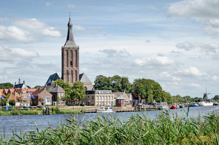 Hasselt, The Netherlands, August 2, 2020: view of the town's waterfront, dominated by Saint Staphanus church, with the windmill in the background 新闻类图片