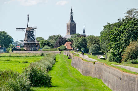 Hasselt, The Netherlands, August 2, 2020: view from the south with the windmill, church and the old brick sea barrier