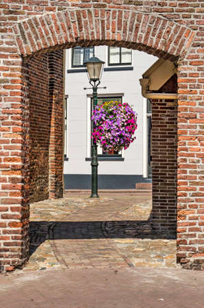 Hasselt, The Netherlands, August 2, 2020: View through a gate in a brick wall towards a street with white plastered houses and a lantern with seasonal flowers 新闻类图片