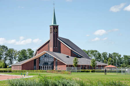 Genemuiden, The Netherlands, August 2, 2020: the large brick building of the Bethel church, completed in 2012, in its green surroundings