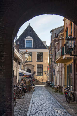 Kampen, The Netherlands, July 30, 2020: looking through the gate underneath the clock tower into the narrow Torenstraat (tower street) 新闻类图片