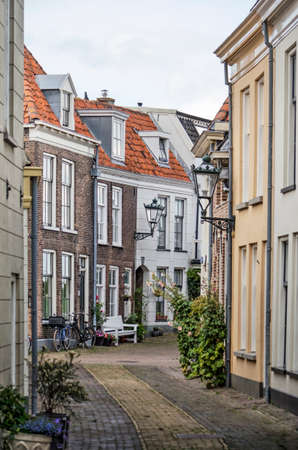 Kampen, The Netherlands, July 26, 2020: narrow curving street in the old town with traditional brick and plaster houses 新闻类图片