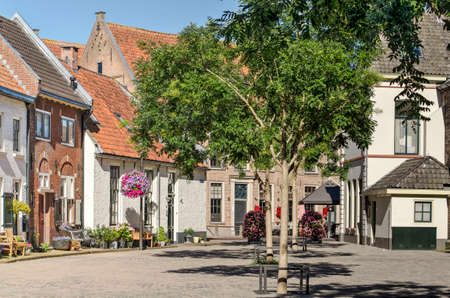 Hattem, The Netherlands, July 31, 2020: the picturesque Krkplein (church square) with trees, and brick and plaster houses in the old town 新闻类图片