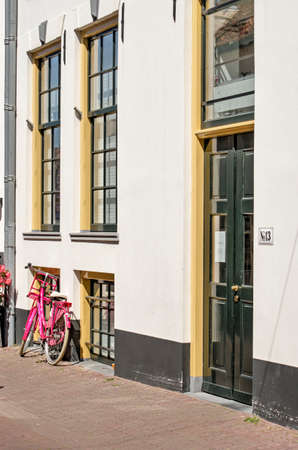 Hattem, The Netherlands, July 31, 2020: Facade in the old town with white plaster and green and yellow window frames and a pink bicycle