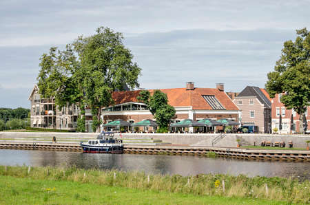 Dalfsen, The Netherlands, August 3, 2020: view across the river Vecht towards the towns recntly refurbished warterfront with architecture in traditional style 新闻类图片