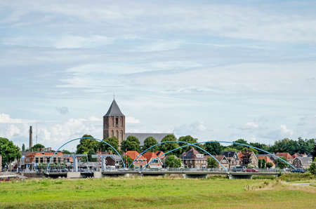 Dalfsen, The Netherlands, August 3, 2020: the protestant church towering over the town's waterfront and the bridge across the river Vecht