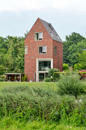 Zwolle, The Netherlands, July 27, 2020: luxury four storey house with a traditional shape and modern elements in a green environment 新闻类图片
