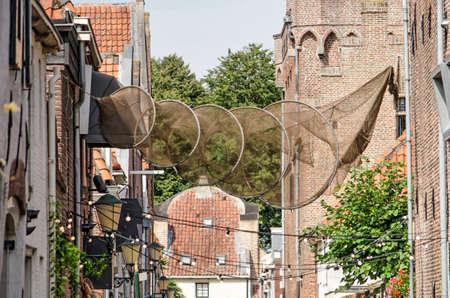 Elburg, The Netherlands, July 30, 2020: Fishing net suspended in a street in the old town, as a reference to the town's history