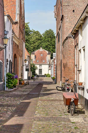 Elburg, The Netherlands, July 30, 2020: bicycles, brick and plaster houses and cobblestone pavement in a narrow street in the old fortified town 新闻类图片