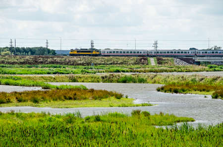 Kampen, The Netherlands, July 26, 2020: view across the wetlands around the new Reevediep river channel with in the background a bridge with a train bound for Germany 免版税图像