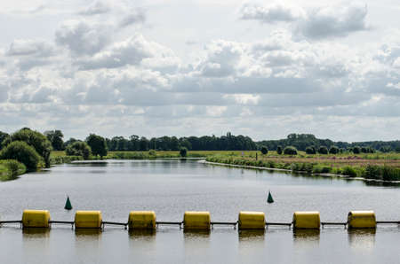 Yellow steel cylinders as a barrier in the river Vecht near Zwolle, The Netherlands to keep boats away from the barrage 免版税图像