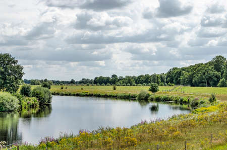 Bend in the river Vecht near Zwolle, The Netherlands in a green landscape under a dramatic sky on a summer day