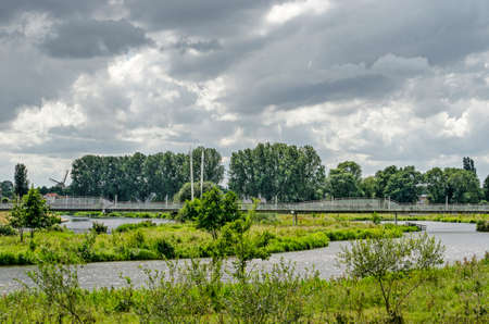 Hardenberg, The Netherlands, July 28, 2020: view across the park in the floodplains of the river Vecht towards the princess amalia bridge for pedestrians and cyclists 免版税图像