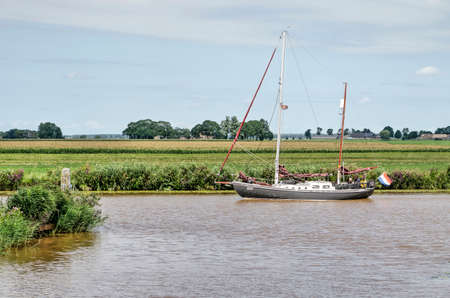 Kamperzeedijk, The Netherlands, August 2, 2020: sailing yacht navigating by motor in a canal in a characteristic frlat green Dutch polder landscape