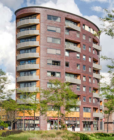 The Hague, The Netherlands, August 23, 2020: residential tower in Wateringseveld neighborhood with an elliptic floorplan and shops on the ground floor