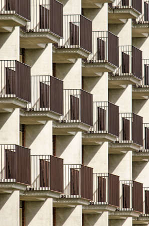 Lansingerland, The Netherlands, August 29, 2020: sun, shadow, balconies and separation walls creating a geometric pattern on the facade of an apartment building