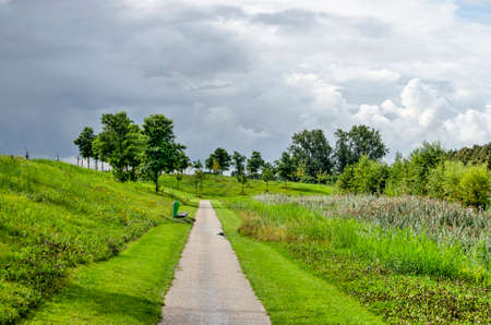 Dramatic sky with approaching rain clouds over a footpath in the new Annie MG Schmidt Park in Berkel en Rodenrijs, The Netherlands