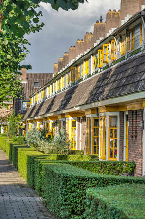 Delft, The Netherlands, August 23, 2020: row of historic townhouses in Amsterdam School style, in the 1920's extension of garden village Agnetapark