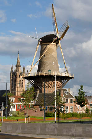 Delft, The Netherlands, August 23, 2020: view of reconstructed Phoenixstraat at the perimeter of the old town with windmill De Roos and the Old Church