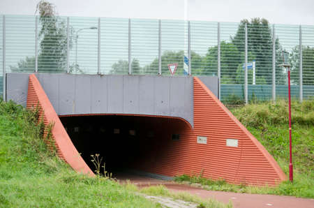 Berkel en Rodenrijs, The Netherlands, August 29, 2020: subway for cyclists and pedestrians under road with transparent sound barrier