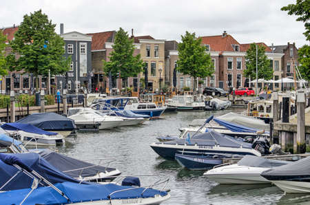 Oud-Beijerland, The Netherlands, July 10, 2020: the town's marina with small yachts and sloop and in the background a row of traditional houses