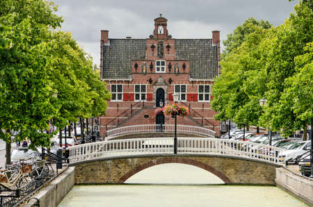 Oud-Beijerland, The Netherlands, July 10, 2020: the picturesque town hall on the axis of the tree-lined Voostraat canal