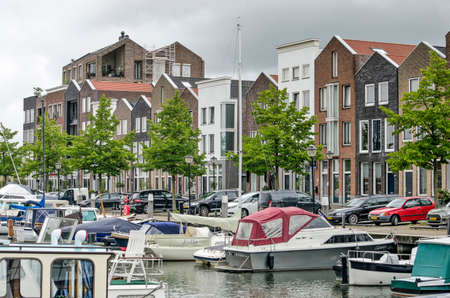 Oud-Beijerland, The Netherlands, July 10, 2020: marina with small yachts and a row of recent houses inspired by traditional architecture 新闻类图片
