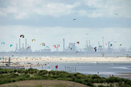 The Hague, The Netherlands, August 29, 2020: long distance view along the sandy coast towards Maasvlakte industrial area, with beach, dunes and kitesurfers