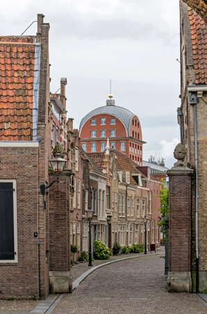 Dordrecht, The Netherlands, August 19, 2020: historic houses in the slightly curving Hofstraat in the old town with a post-modern residential building in the background