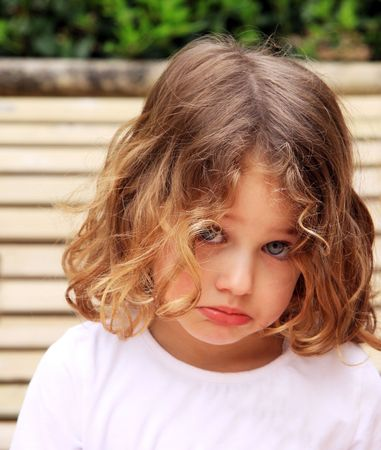 a young child with a pretty face sulking and pouting against a natural background Stock Photo