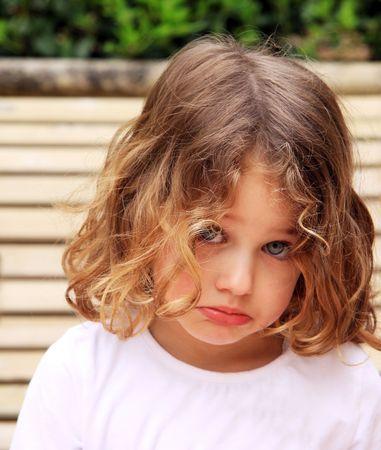 un bambino piccolo con un bel viso imbronciato sulking e nei confronti di un fondo naturale Archivio Fotografico