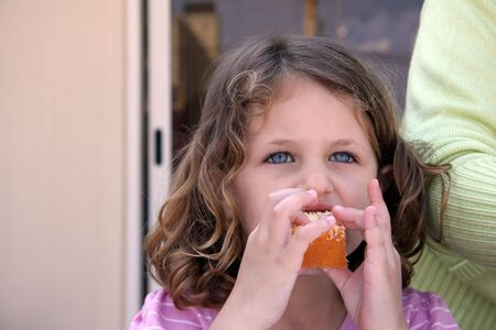 a candid shot of a pretty girl with blue eyes and wavy hair eating birthday cake with two hands Stock Photo - 4986487