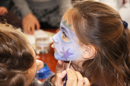 a child getting her face painted at a party