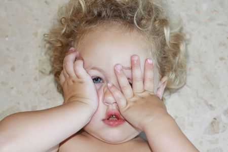 in twos: a toddler lying on the floor throwing a terrible twos tantrum and covering her face with her two hands