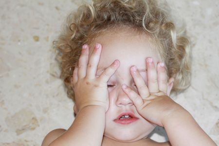 a child lying on the floor upset with hands covering her face Stock Photo
