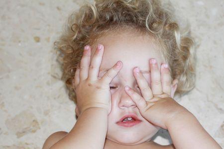un bambino disteso sul pavimento sconvolto con le mani che coprono il viso
