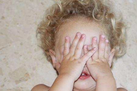 un bambino disteso sulla schiena sul pavimento con il viso coperto dalle sue mani, con profondit� di campo e concentrarsi sulle mani del bambino