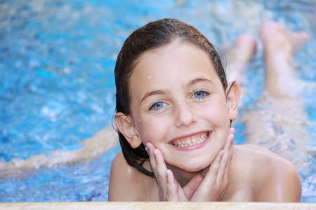 a girl lying down in a swimming pool with splashes of water on her face looking at the camera smiling